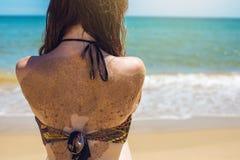 Donna che si siede sulla spiaggia sabbiosa e sugli sguardi fuori al mare Immagine Stock Libera da Diritti