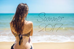 Donna che si siede sulla spiaggia sabbiosa e sugli sguardi fuori al mare Fotografie Stock Libere da Diritti