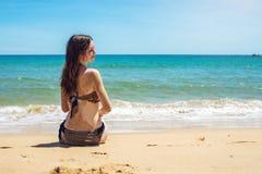 Donna che si siede sulla spiaggia sabbiosa e sugli sguardi fuori al mare Fotografia Stock Libera da Diritti