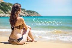 Donna che si siede sulla spiaggia sabbiosa e sugli sguardi fuori al mare Fotografia Stock