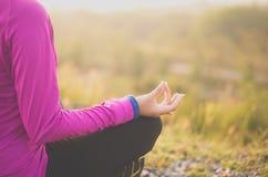 Donna che si siede sulla strada che pratica facendo esercizio e allenamento di yoga, concetto di stile di vita e sano Fotografie Stock