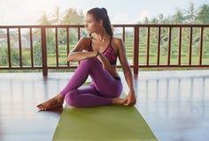 Donna che si siede sulla stuoia e sul distogliere lo sguardo di yoga Immagine Stock