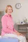 Donna che si siede sulla tabella dell'esame durante il controllo immagini stock