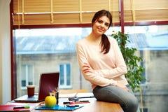 Donna che si siede sulla tavola nel suo luogo di lavoro Fotografie Stock