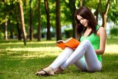Donna che si siede sulla terra e sul libro di lettura fotografie stock