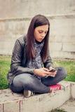 Donna che si siede sulla via della città, messaggio di battitura a macchina, chiacchierante sullo smartp Fotografia Stock Libera da Diritti