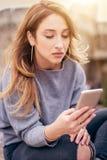 Donna che si siede sulla via della città, messaggio di battitura a macchina, chiacchierante sullo smartp Immagini Stock