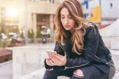 Donna che si siede sulla via della città, messaggio di battitura a macchina, chiacchierante sullo smartp Fotografia Stock