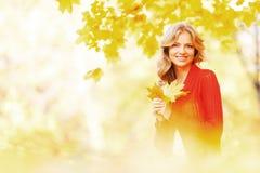 Donna che si siede sulle foglie di autunno Fotografia Stock Libera da Diritti