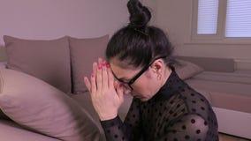 Donna che si siede sulle ginocchia e sul pregare video d archivio