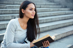 Donna che si siede sulle scale della città con il libro all'aperto Fotografie Stock Libere da Diritti
