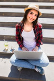 donna che si siede sulle scale della città e che per mezzo del computer portatile Fotografie Stock Libere da Diritti