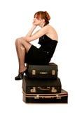 Donna che si siede sulle valigie Immagini Stock