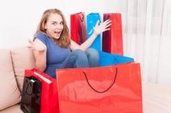 Donna che si siede sullo strato con il sacchetto della spesa intorno ad agire allegro Immagini Stock Libere da Diritti