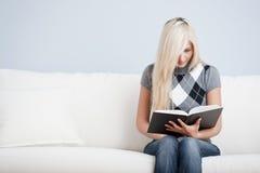 Donna che si siede sullo strato e sul libro di lettura Immagine Stock