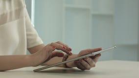 Donna che si siede in tavola dell'ufficio e compressa di tocco