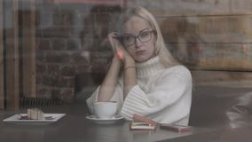 Donna che si siede in un caffè Caffè bevente e sognare archivi video