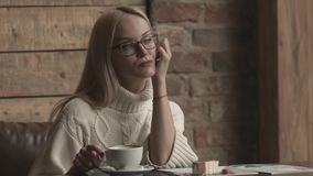 Donna che si siede in un caffè Distogliendo lo sguardo, caffè bevente video d archivio