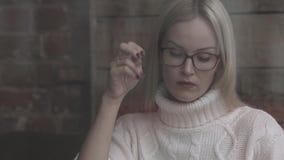 Donna che si siede in un caffè Distogliendo lo sguardo e per mezzo di uno smartphone archivi video