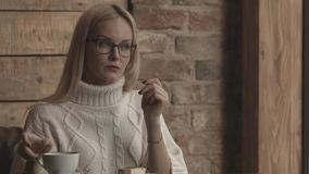 Donna che si siede in un caffè Distogliere lo sguardo caffè bevente video d archivio