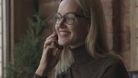 Donna che si siede in un caffè Parlando sullo smartphone e sognare stock footage
