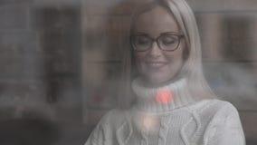 Donna che si siede in un caffè Parlando sullo smartphone e sul caffè bevente stock footage