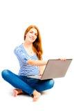 Donna che si siede in una posizione di loto con un computer portatile Fotografia Stock Libera da Diritti