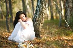 Donna che si siede vicino all'albero Fotografia Stock Libera da Diritti