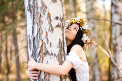 Donna che si siede vicino all'albero Immagine Stock