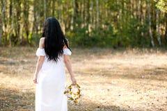 Donna che si siede vicino all'albero Fotografia Stock