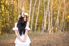Donna che si siede vicino all'albero Fotografie Stock