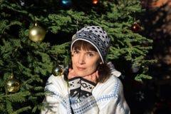 Donna che si siede vicino all'albero di Natale Immagine Stock Libera da Diritti