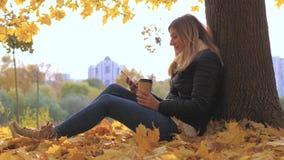 Donna che si siede vicino all'albero in foglie gialle di caduta, usi Apps e caffè bevente video d archivio