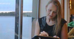 Donna che si siede vicino alla finestra e che per mezzo della compressa archivi video