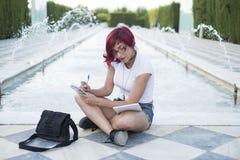 Donna che si siede vicino alle note di una fontana con un taccuino Fotografie Stock Libere da Diritti