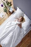 Donna che si situa a letto Fotografia Stock