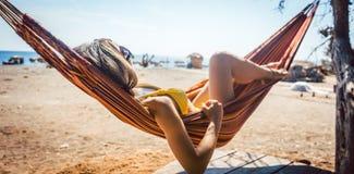 Donna che si trova in amaca vicino alla spiaggia immagini stock libere da diritti