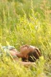 Donna che si trova nell'erba Fotografia Stock Libera da Diritti
