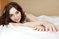 Donna che si trova nella base sulle coperte da letto bianche Immagini Stock Libere da Diritti