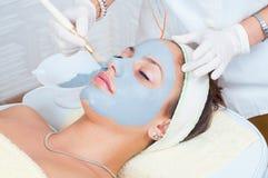 Donna che si trova nella stazione termale di salute mentre la maschera facciale è messa sul suo fronte fotografia stock