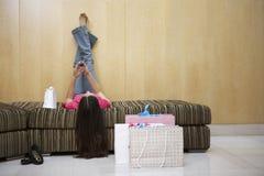 Donna che si trova su Sofa While Text Messaging fotografie stock libere da diritti