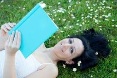 Donna che si trova su un prato fiorito che legge un libro Fotografia Stock Libera da Diritti