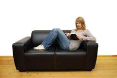 Donna che si trova su un sofà e che legge un libro immagine stock libera da diritti