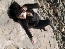 Donna che si trova su una roccia Fotografia Stock
