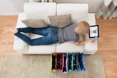 Donna che si trova sui sacchetti della spesa di Sofa With Digital Tablet And Fotografie Stock