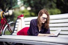 Donna che si trova sul banco e sul libro colto Fotografie Stock