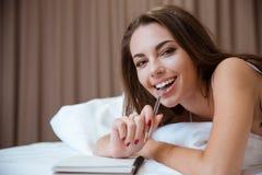 Donna che si trova sul letto con la penna ed il blocco note Immagine Stock Libera da Diritti