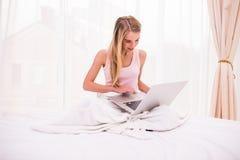 donna che si trova sul letto e che per mezzo del computer portatile Immagini Stock Libere da Diritti