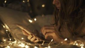 Donna che si trova sul letto ed utilizzare telefono per chiacchierata stock footage