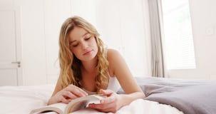 Donna che si trova sul letto mentre leggendo romanzo archivi video